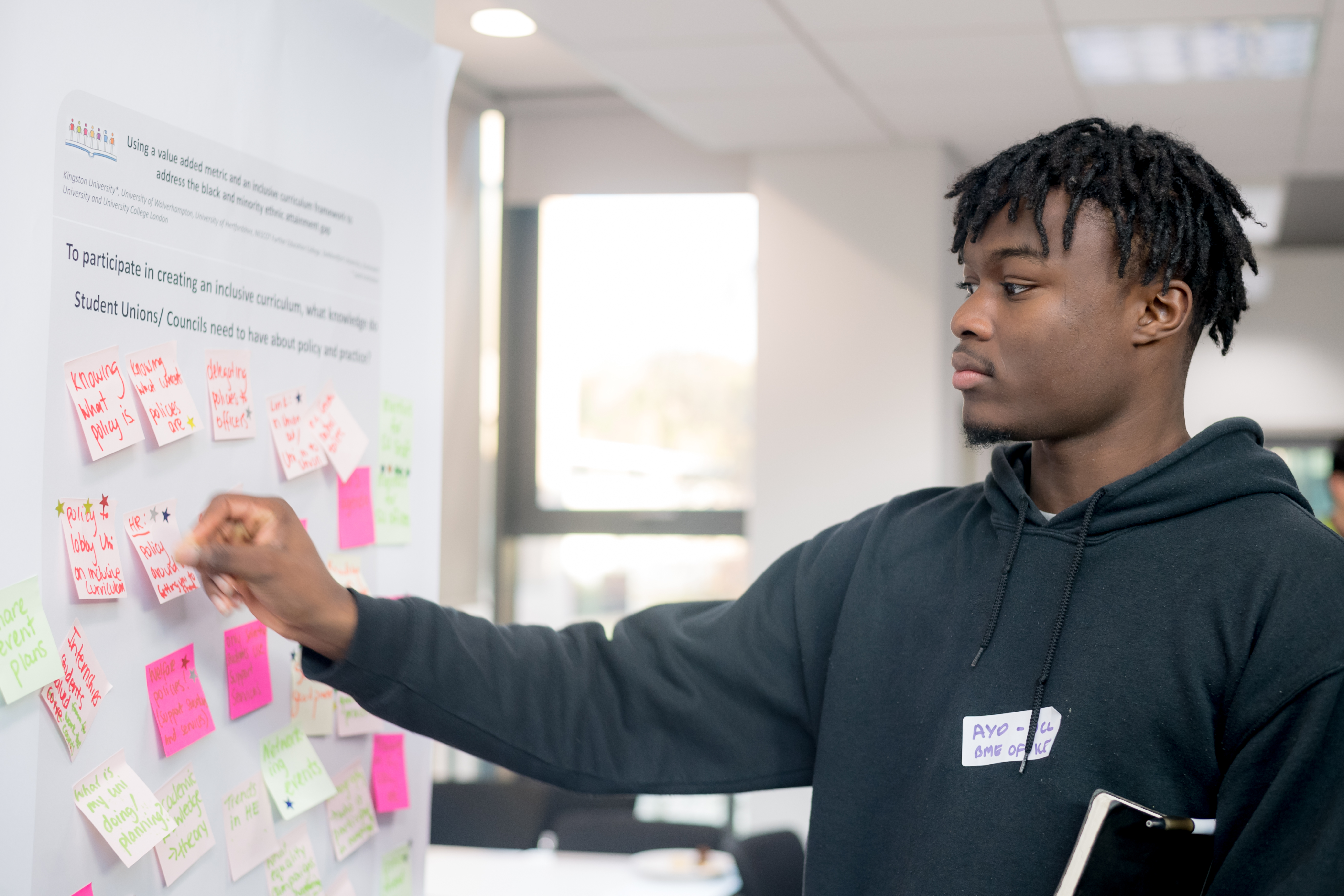 Student adding a post it note to a board