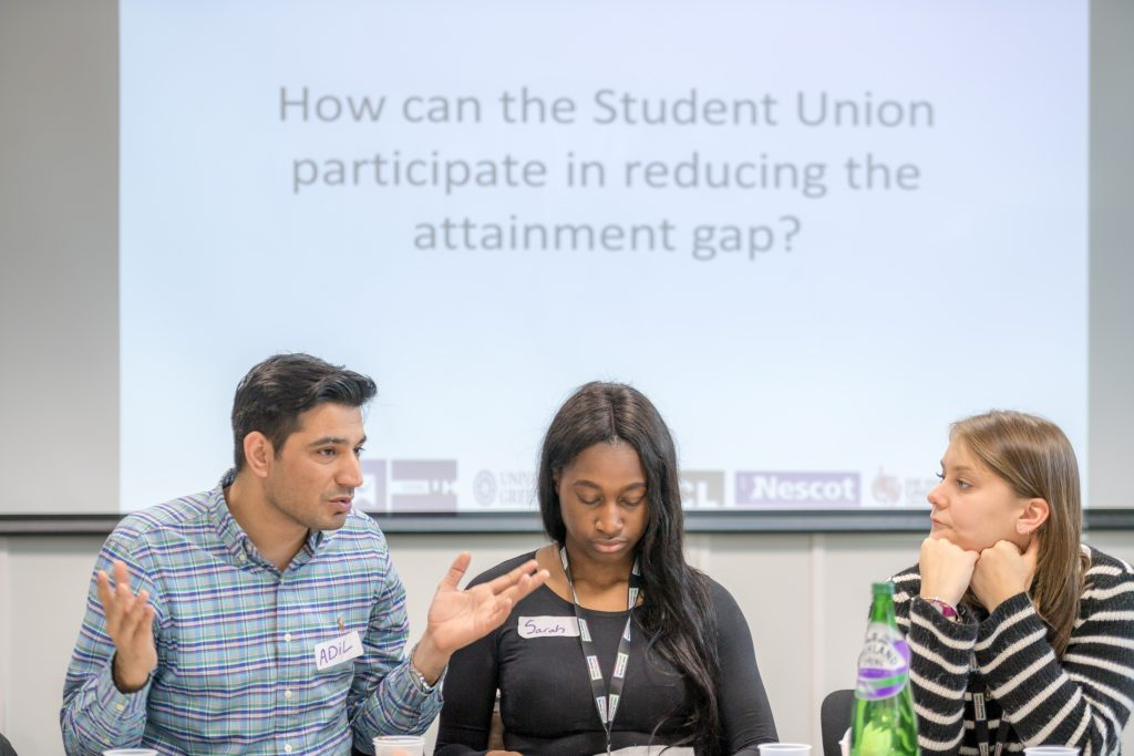 Three students sitting in front of a presentation.